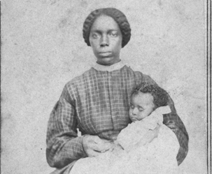 Ethnic: Full-length portrait of an African American woman seated holding an African American infant